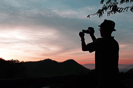 sunup: Digital video camera Selected focus which is held by a man who wears a hat,an eye glasses with some mountains,tree and gradient orange-blue sky view while before sunrise silhouette mode Stock Photo