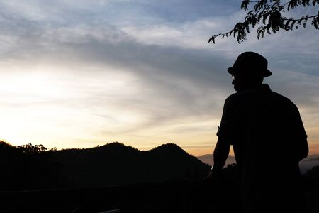 wanderers: a man who wears a hat,an eye glasses Selected focus with some mountains,tree and gradient light orange-blue sky while before sunrise silhouette mode