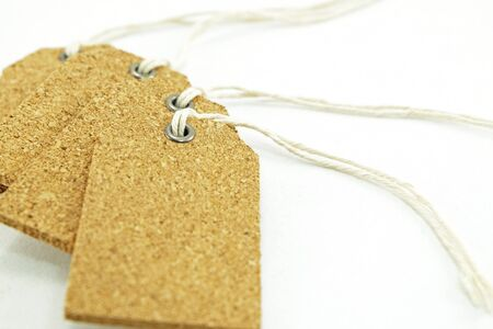 eyelet: steel eyelet (Selected focus) of the front plywood tag label with hanging packthread with others on white background