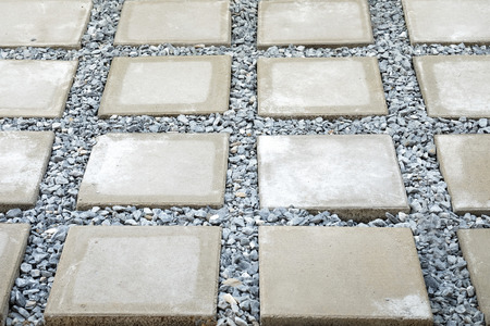 flagstone: rectangular concrete flagstone,is selected focus at left and above of the frame,with other flagstones and  strew around each flagstone by stones Stock Photo