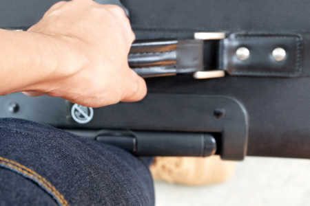 tendons: Tendons (selected focus) at wrist while carrying a black baggage with a brown boot and jeans Stock Photo