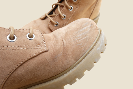 the abrasion at toe box of one flannel boots with another one (with light brown background and have clipping path)