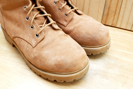 eyelet (selected focus) of left flannel boots which have the abrasion at toe box with another one on wood background