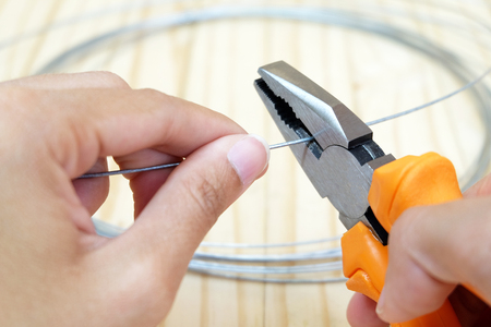 wire cutter: wire,is cut by wire cutter head with orange color handle with wood ground,is hold by hand Stock Photo