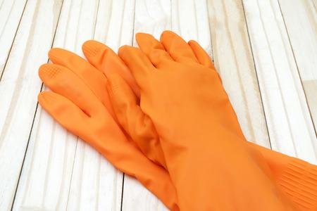 rubber gloves: orange color rubber gloves on wood ground