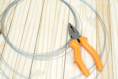 wire cutter: wire cutter head (Selective focus) with orange color handle which on wire roll and wood ground