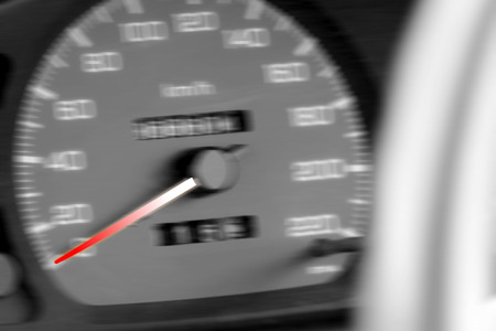 evident: gradient red-white color speedometer needle points at zero kmhr in speedometer gauge in blur and black-white mode Stock Photo