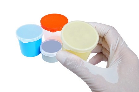 specimen testing: yellow urine container with lid held by hand with other urine and sputum collection containers in many size and color on white ground (isolated and have clipping path) Stock Photo