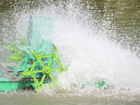 dissolved: center of the core of green PADDLE WHEEL AERATOR with water splash is working in pool (little moving mode) Stock Photo