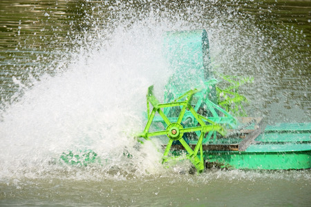 aerator: core of green PADDLE WHEEL AERATOR with water splash is working in pool (moving mode with little blur)