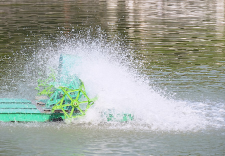 aerator: core of green PADDLE WHEEL AERATOR with water splash is working in pool (moving and little blur mode)