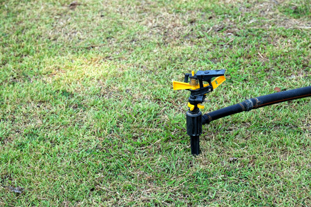 yellow and black garden sprinkler is set on the grass Lawn