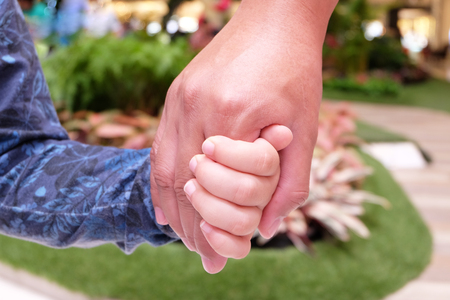 leashes: father leashes hands son with blue park garden background (center of frame is selected focus) Stock Photo