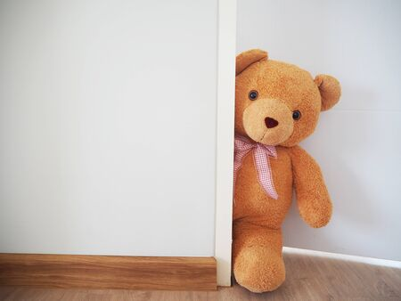 Background for kids play Teddy bear, brown hair standing behind the wall. Hide the secret of children 版權商用圖片