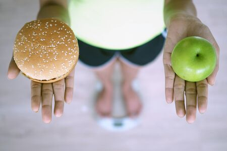 Women are weighing with scales, holding apples and hamburgers. The decision to choose junk food that is not good for health and fruits that are high in vitamin C is good for the body. Diet concept 版權商用圖片