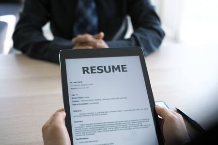 Executives are interviewing and watching the resume via tablet. Focus on resume writing tips, applicant qualifications, interview skills and preparation before the interview.