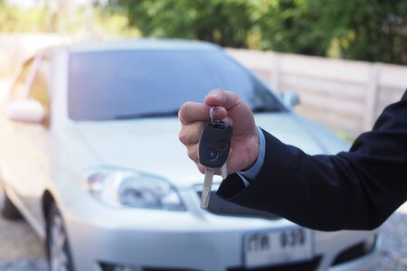 The car salesman and the key to the new owner. Stock fotó