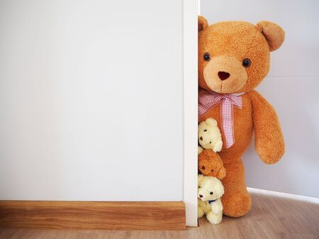 Background for children. The teddy bear family is standing behind the wall. 版權商用圖片
