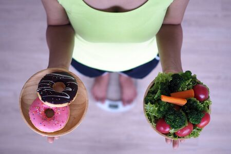 Women are weighing with the scales, holding donuts and salads. The decision to choose junk food that is not good for health and high vitamin vegetable is beneficial to the body.