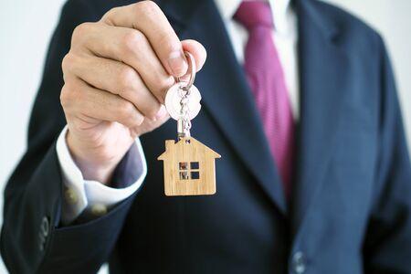 Los agentes de venta de viviendas están dando las llaves de la vivienda a los nuevos propietarios. Propietarios y concepto de llaves de casa. Foto de archivo