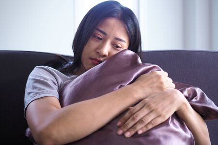 An Asian woman with mental pain is sitting alone hugging a pillow. 스톡 콘텐츠