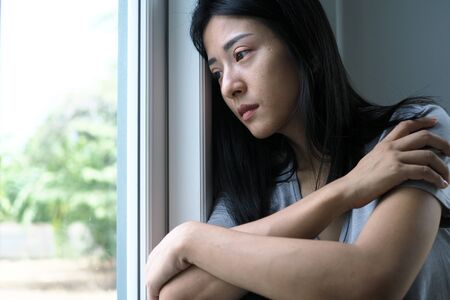Asian woman sitting inside the house looking out at the window. Foto de archivo - 140691687