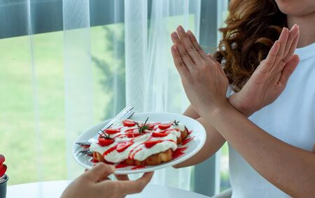 Healthy women refuse to eat bread containing whipped cream and cheese. No carbohydrate and trans fats for good shape and good health.
