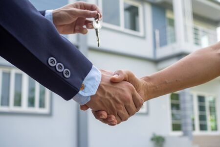 Agent sells the house shake hand with the buyer and send house key to the buyer.