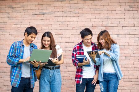 A group of cheerful and happy teens looked at the information on laptops and tablets with fun. University student group concept Foto de archivo - 141759580