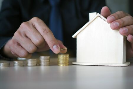 The businessman's hand is holding a coin putting it in a stack and capturing the house model. Financial planning and saving money concept Foto de archivo - 142099736