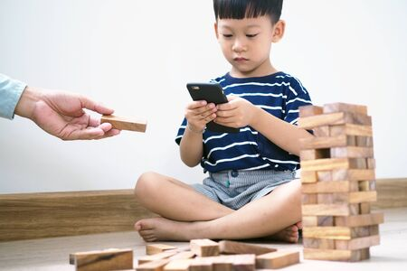 Asian children in the age of social networks that focus on phones or tablets. Do not care about the surrounding environment and have eye problems. Foto de archivo - 142074195