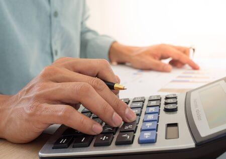 A business man using a calculator to calculate expenses from receipts placed on the table. debt concept Foto de archivo - 142099768