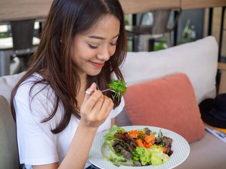 Asian women are happy to eat salmon salad. Food for good health Foto de archivo - 142075308