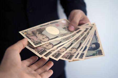 Businessmen send Japanese banknotes to employees. Foto de archivo - 141219511