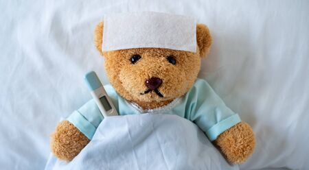The teddy bear is sick on the bed with a high fever. There is a fever reducing sheet on the forehead. Foto de archivo - 141668286
