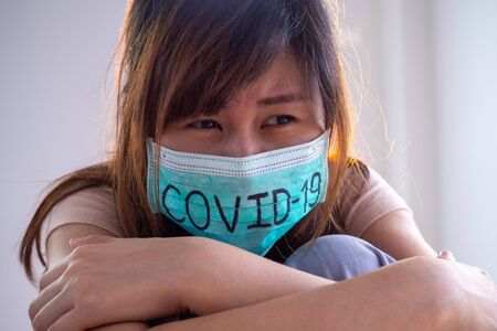 Asian Woman Worry and Fears Wearing Mask, writes Covid-19 The situation of the 2019-nCoV virus infection is spreading all over the world. Deadly plague of the world Masked concept to protect coronavirus