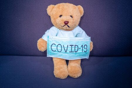 Sick teddy bear with mask writes Covid-19. The situation of the 2019-nCoV virus infection is spreading around the world. Deadly plague of the world. concept wear mask to protect coronavirus