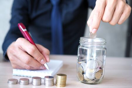 Businessmen holding coins in a glass jar and record financial accounting. Financial planning and saving money concept