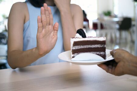 One of the health-care girls used a hand to push a plate of chocolate cake. Refuse to eat foods that contain Trans Fat. Foto de archivo - 142298079