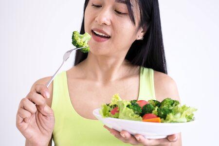 Asian beautiful women are happy to eat salad vegetables. Foto de archivo