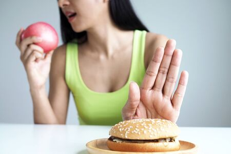 Asian women push the hamburger plate and choose to eat apples for good health.