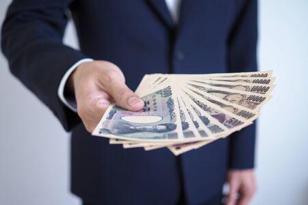 Businessmen sending Japanese yen notes