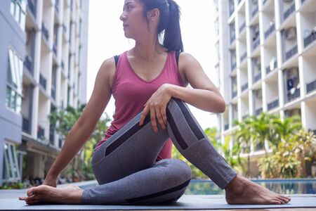 Young women are doing seated twist exercises for health and a firmer body. exercise and relax muscles by the pool. yoga concept
