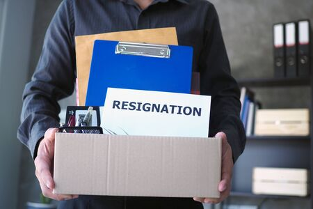 Businessman hold boxes for personal belongings and resignation letters.