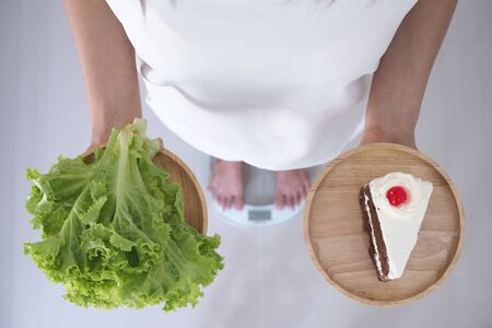 Women weigh themselves on scales and holding vegetables and chocolate cakes. Vegetables are useful to the body and the cake has trans fat. diet concept