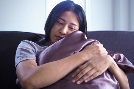 The woman sat and hugged the pillow on the sofa in the house. The expression and despondency and despair.
