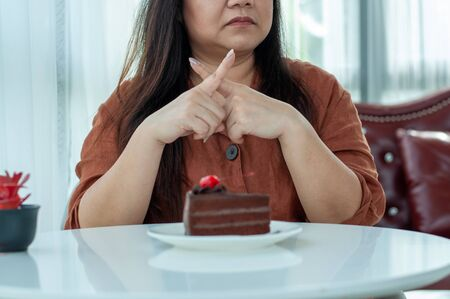 Women in the weight-loss court refused to eat chocolate cakes. Determination to lose weight for good health and good shape Foto de archivo