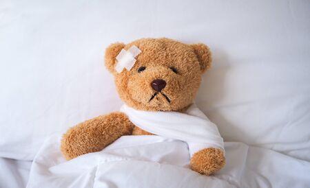 L'ours en peluche est tombé malade dans le lit, blessé par l'accident. notion d'assurance