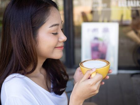 Cute girl enjoying drinking coffee in free time inside the coffee shop with a relaxed gesture with a smile.