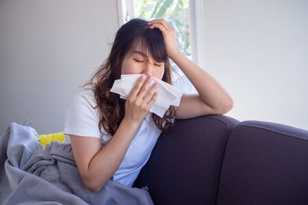 Asian women with dizziness suffer from allergies and cover their nose with tissue paper. Because he was sneezing all the time.
